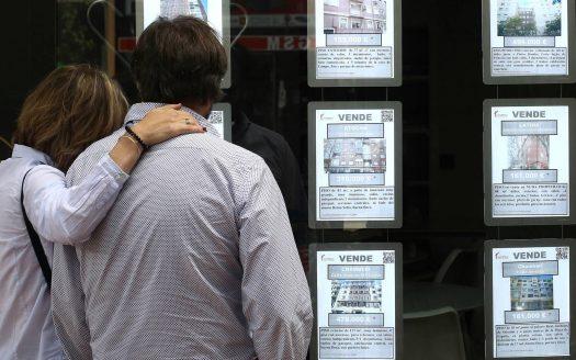 Una pareja observa anuncios de pisos en una inmobiliaria en Madrid (Luis Sevillano)